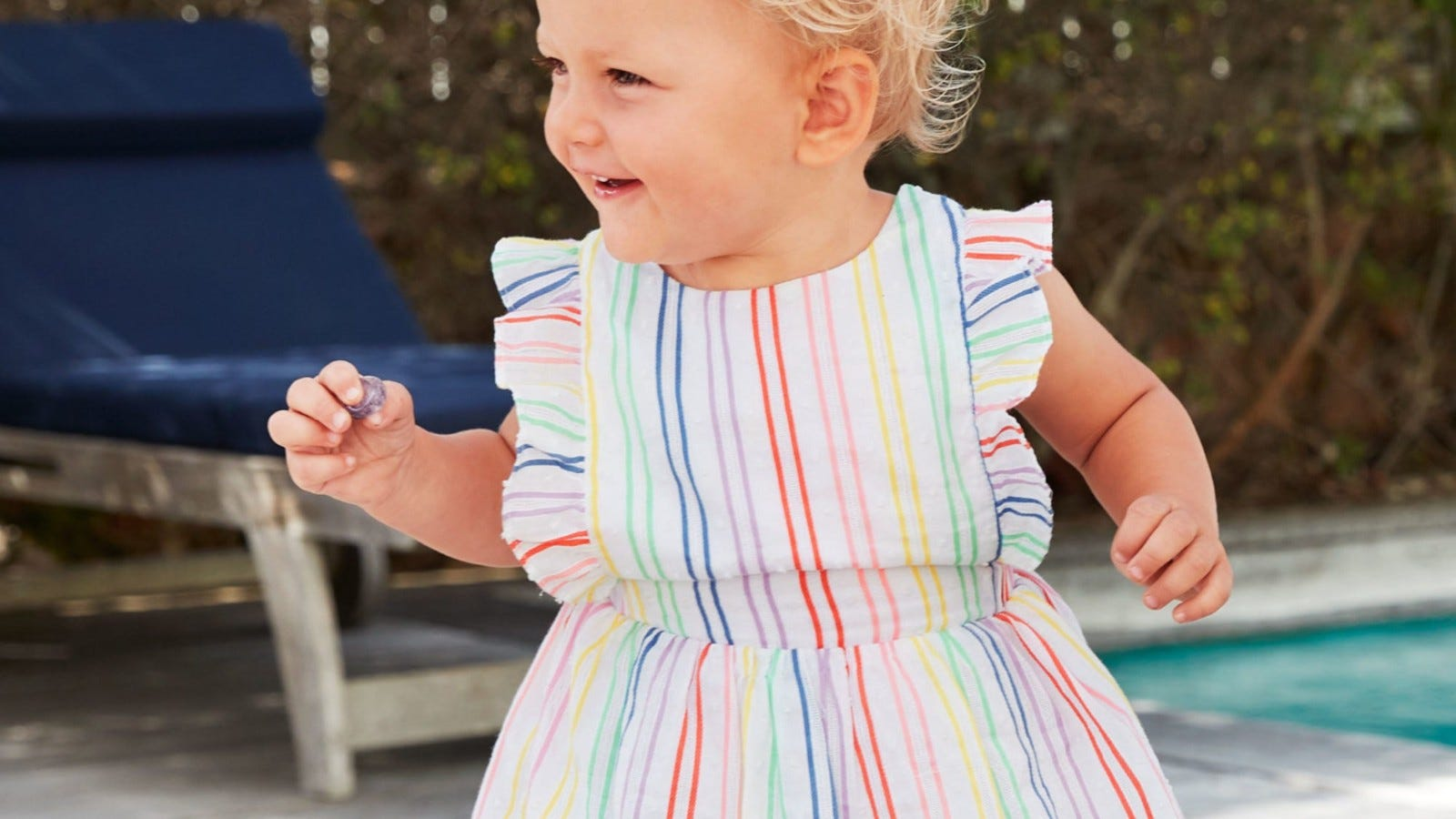 A little girl wearing the Rainbow Stripe Pinafore from Boden.