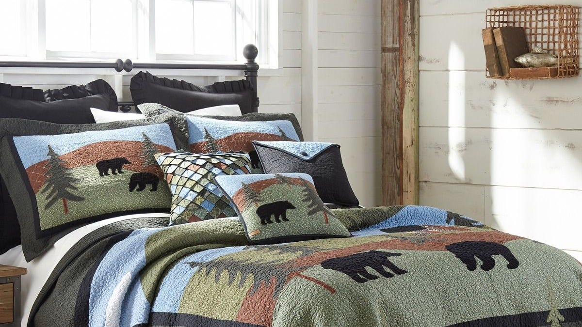 A fall-themed quilt and pillows with a pattern of bears and trees on a bed.
