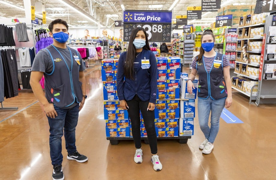 Three Walmart associates stand in front of a display.