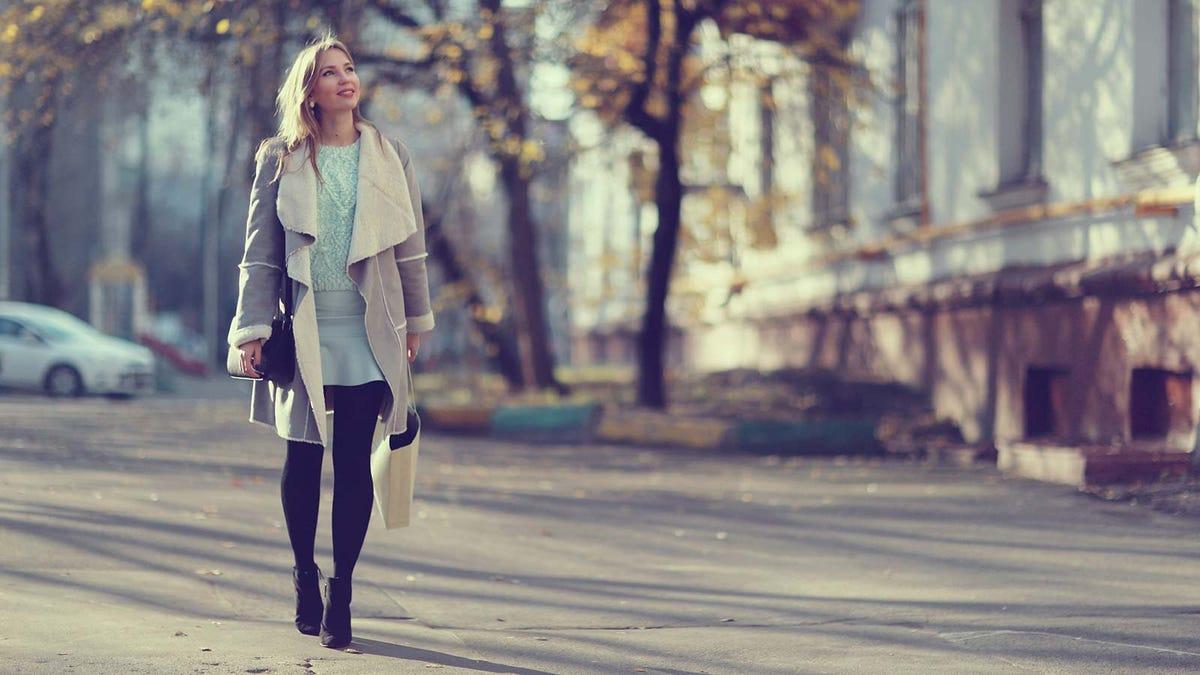 A woman walking down a city street, enjoying the fall air and new sights.