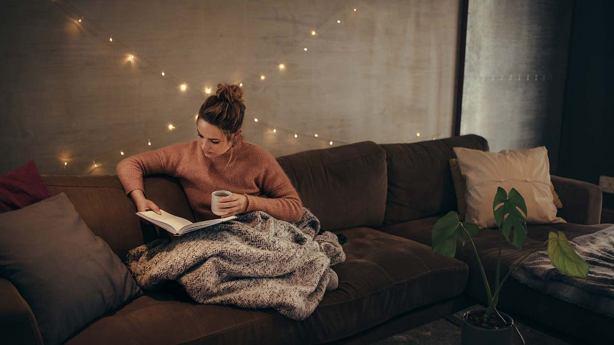 Woman reading in a softly lit room, enjoying a cozy fall drink.
