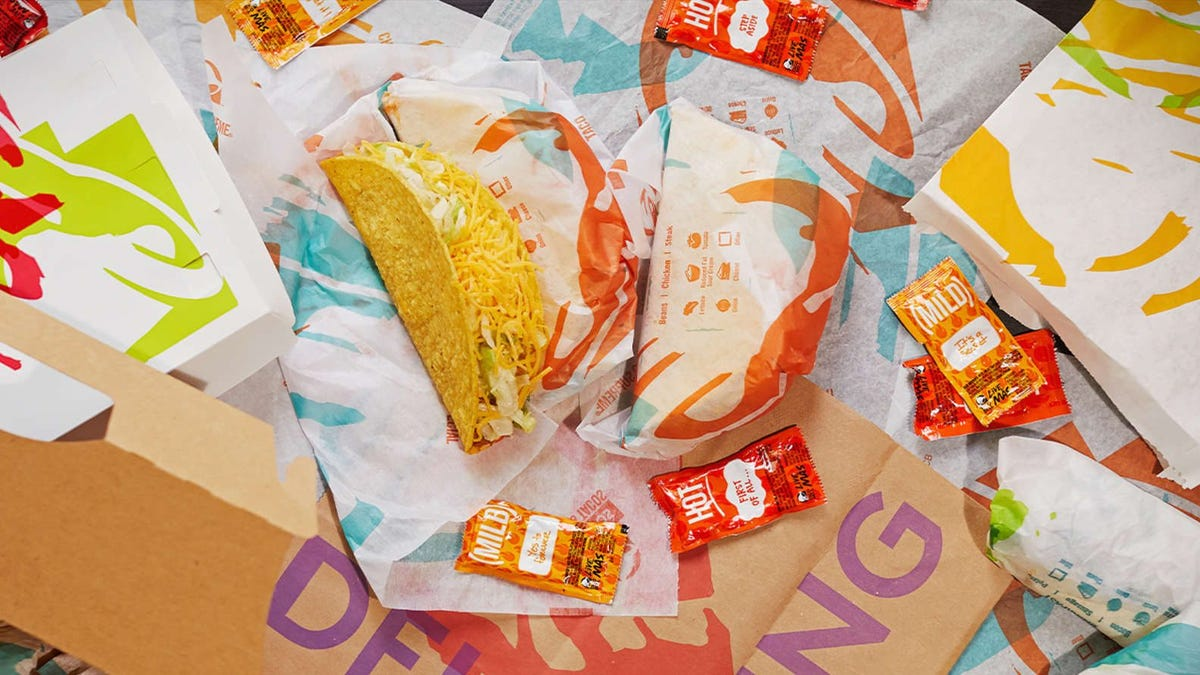 A taco bell taco and chalupa sit among taco bell packaging.