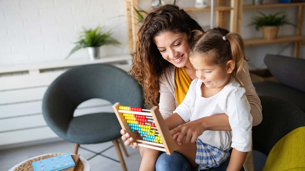 A mom and daughter using an abacus.