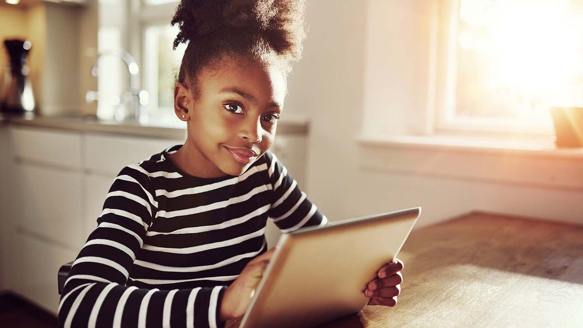 A young girl holding a tablet at the kitchen table.