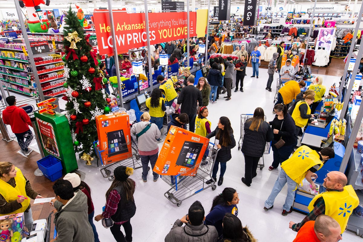 A crowd gathers inside a WalMart with buggies full of sale items.