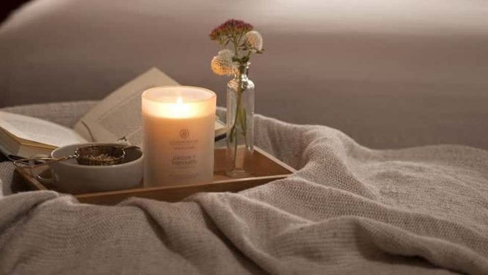 The Chesapeake Bay peace+tranquility candle lit on a tray with flowers.