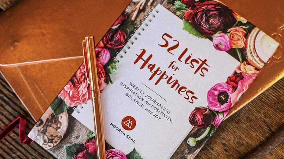 """The book """"52 Lists for Happiness: Weekly Journaling Inspiration for Positivity, Balance, and Joy"""" on a table with a pen on top of it."""
