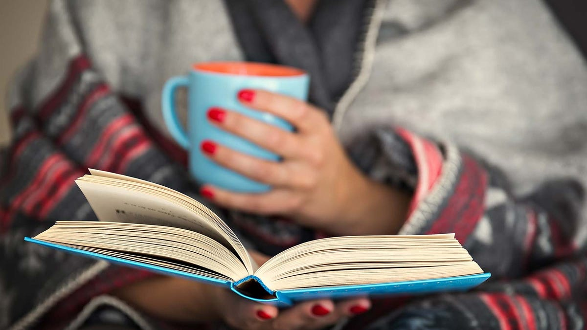 A woman holding a book while drinking from a colorful mug.