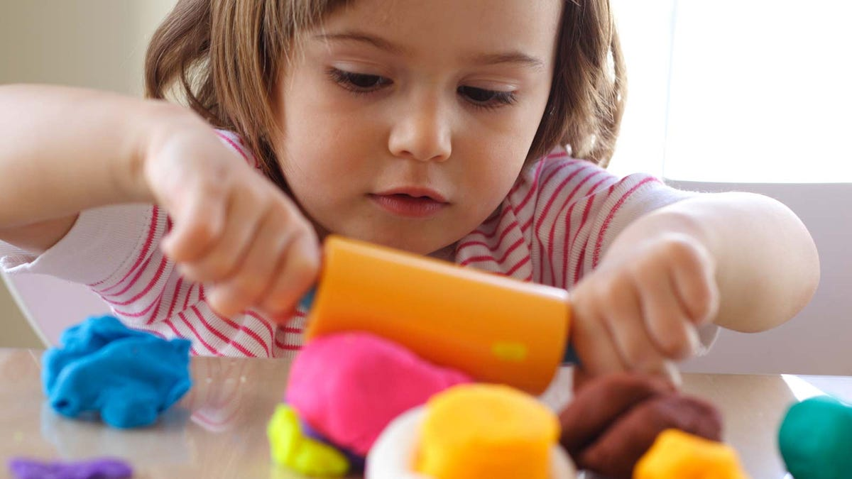 A little girl rolling out Play-Doh on a kitchen counter.