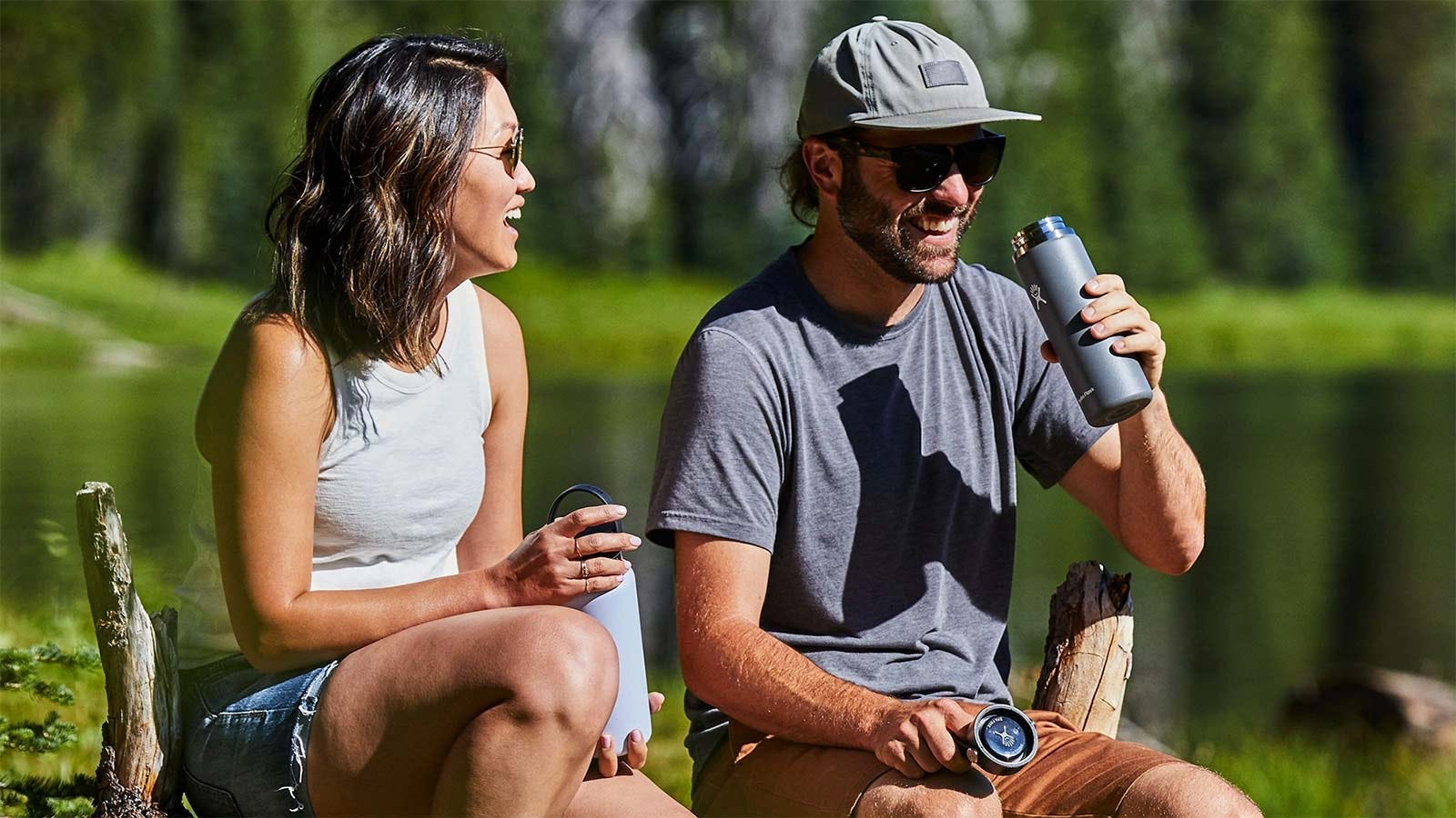 A man and woman holding Hydro Flask water bottles.