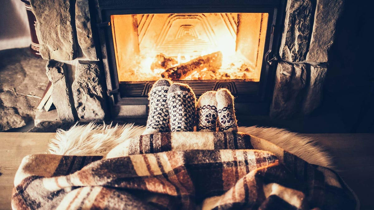 Two pairs of feet in wool socks sticking out of a blanket by a fireplace.