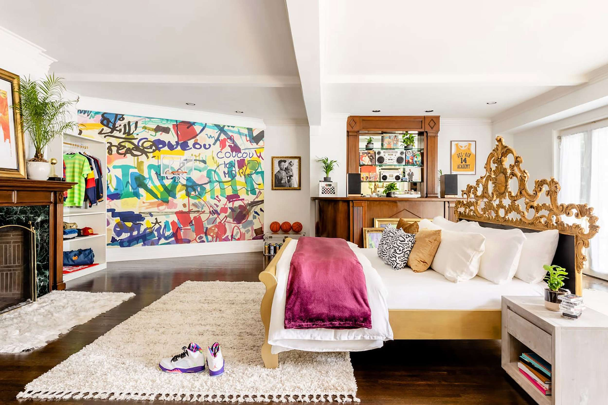 An 80's inspired bedroom features a large bed with a golden bedframe, a graffiti wall, and a boombox station.