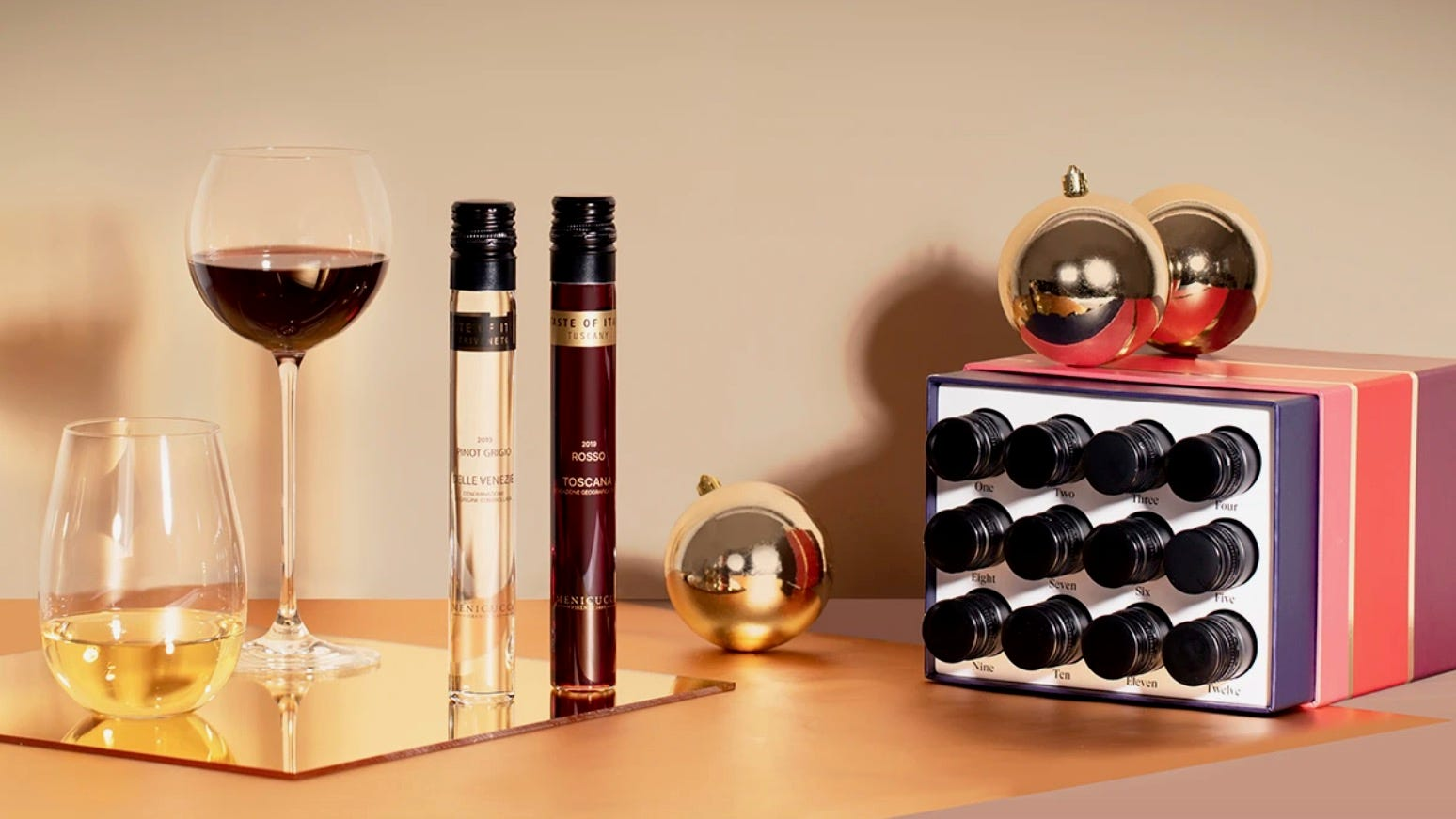 Two glasses and two vials of wine sit next to a wine advent calendar.