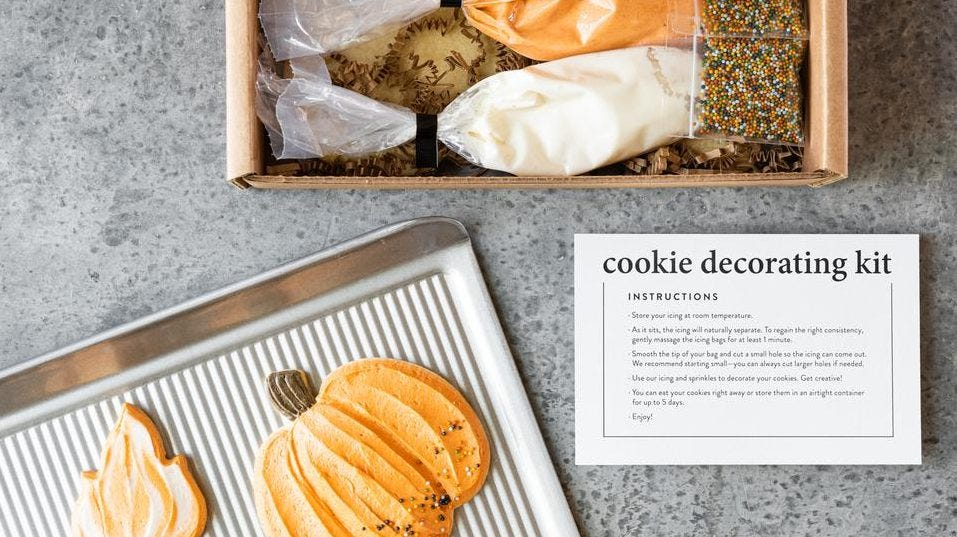 A set of fall-themed cookies decorated with icing sit on a sheet pan with decor tools in a box next to it.