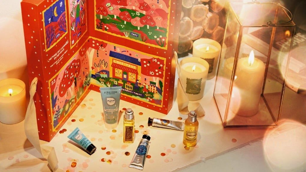 L'Occitane mini products in front of an advent calendar and next to lit holiday candles.