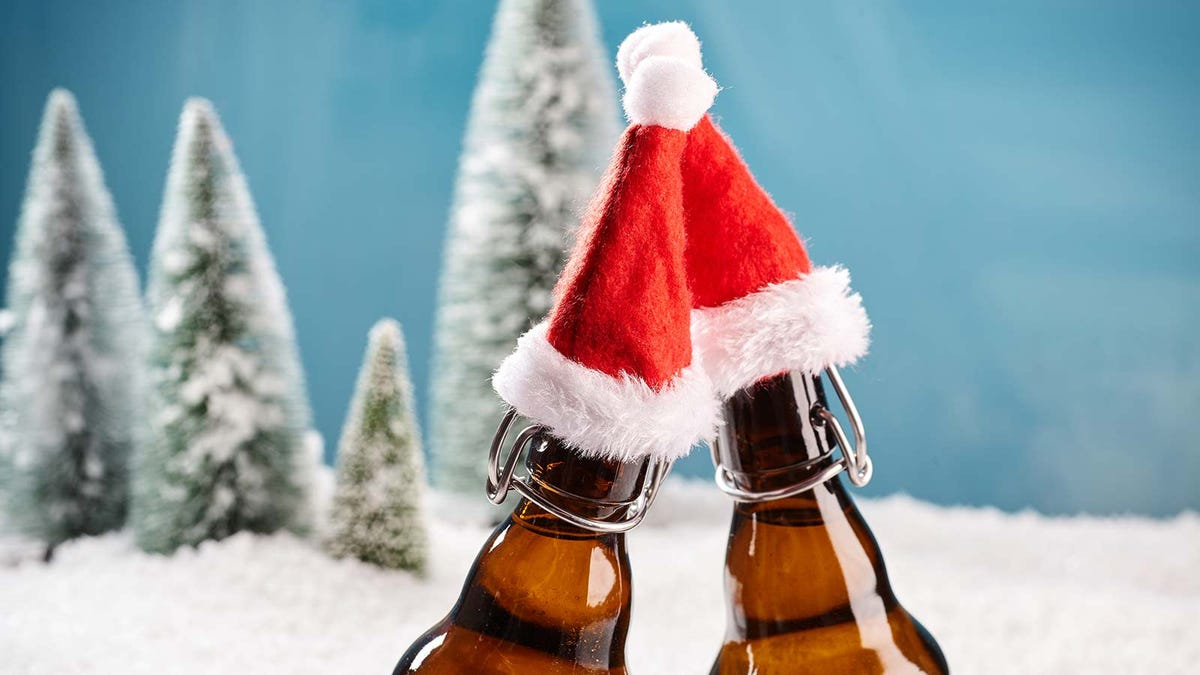 Two beer bottles wearing tiny Santa hats.