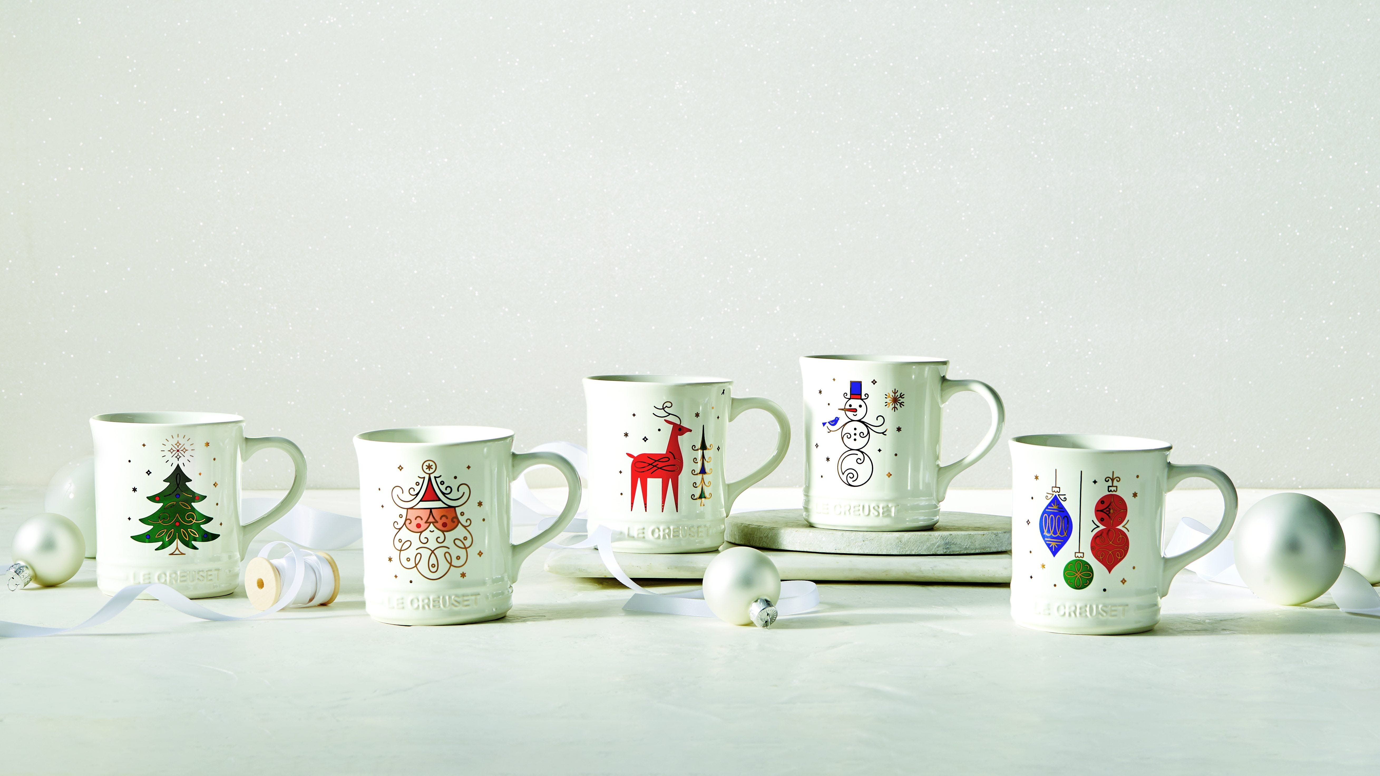 A collection of white mugs with deer, Santa, and ornaments sit arranged on a countertop.