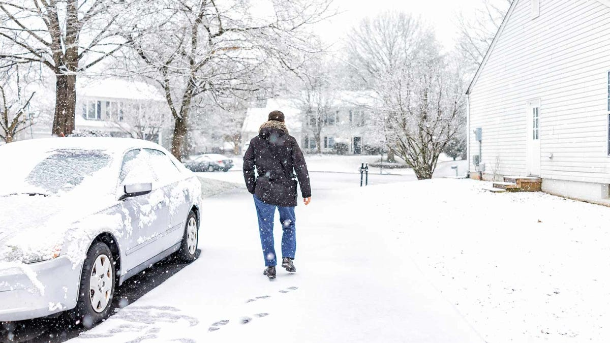 A man walks through falling snow that has coated a car and the ground.