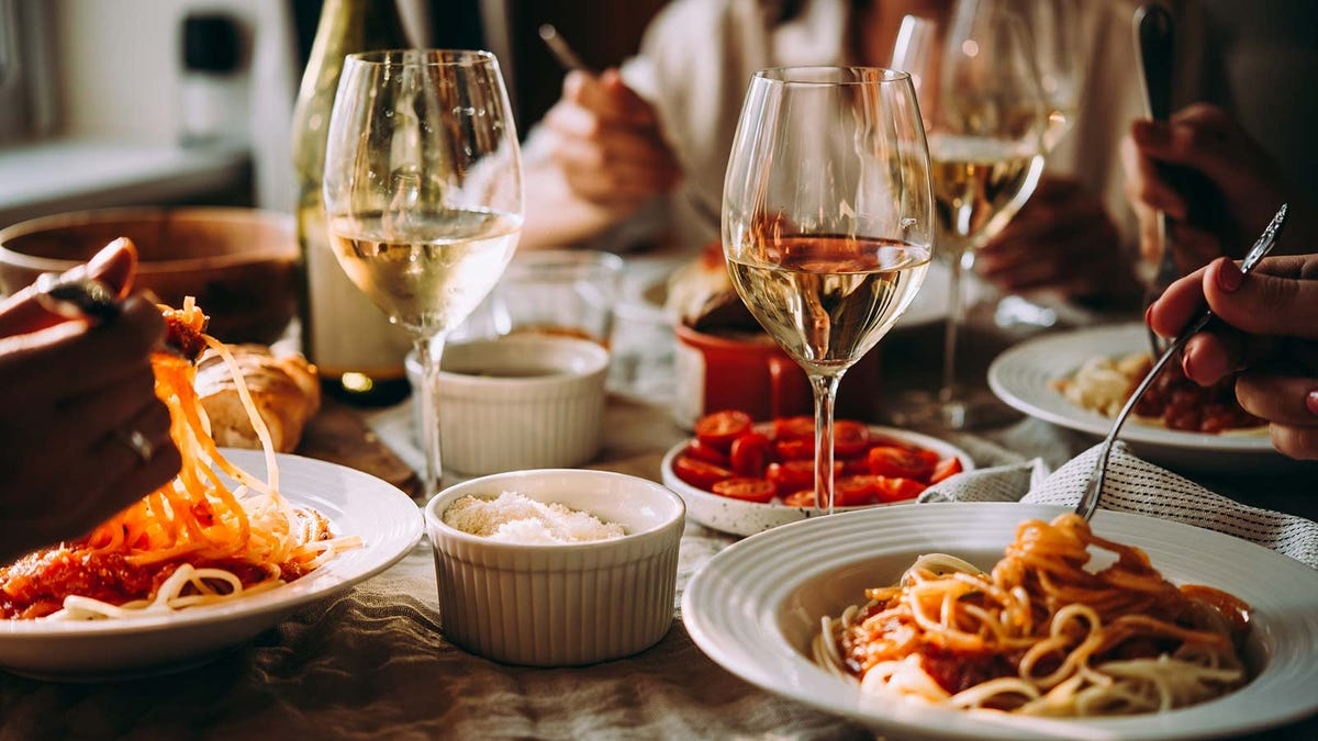 Three people eating spaghetti and drinking white wine at a restaurant.