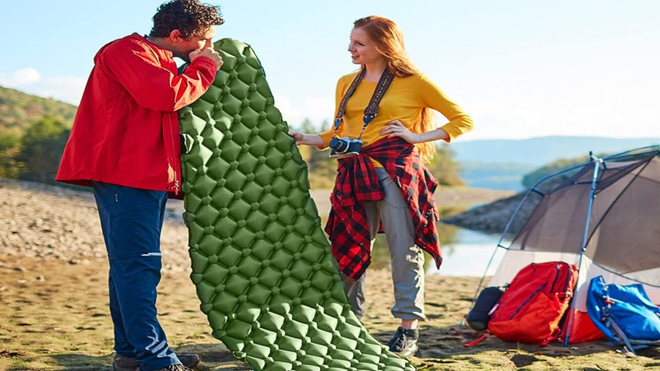 A woman holding a Sleepingo Sleeping Pad while a man blows into it to inflate it.