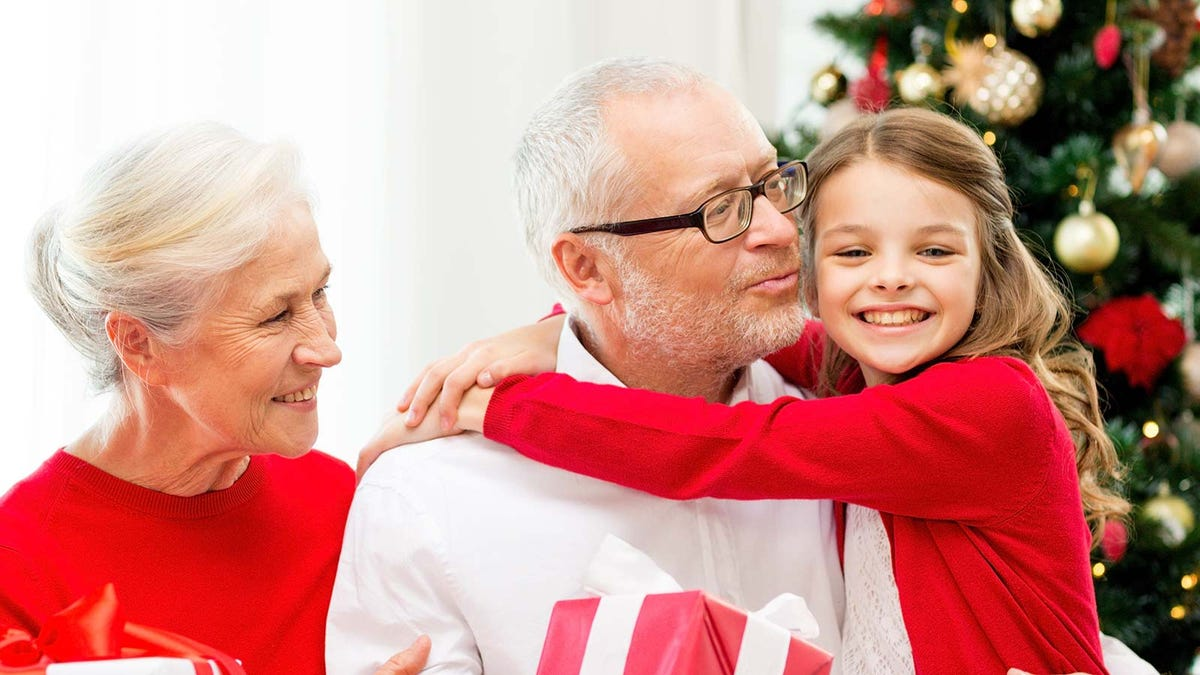 A little girl hugging her grandparents by a Christmas tree.