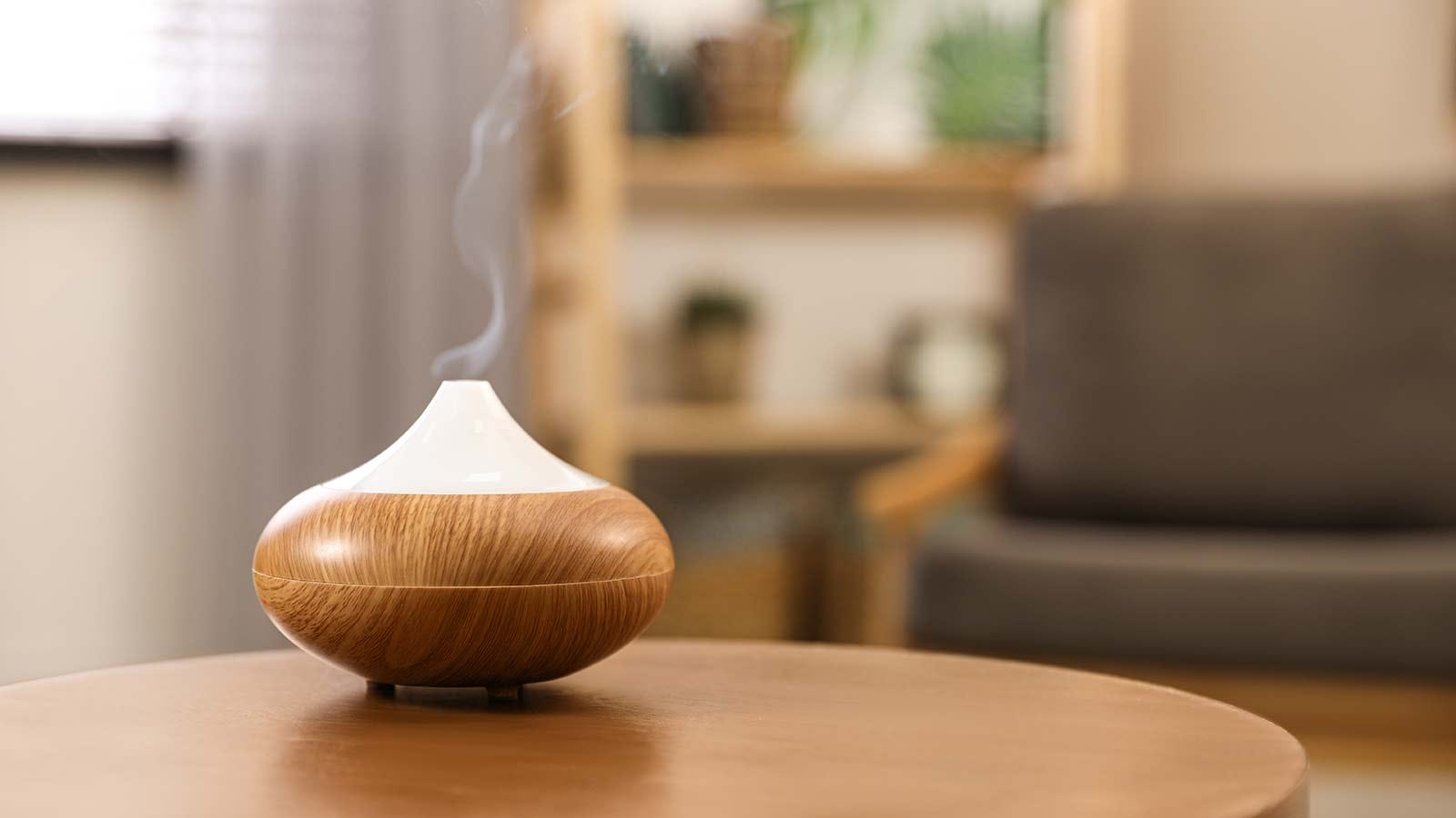 An oil diffuser on a living room table, a fine mist of scent drifting out of it.