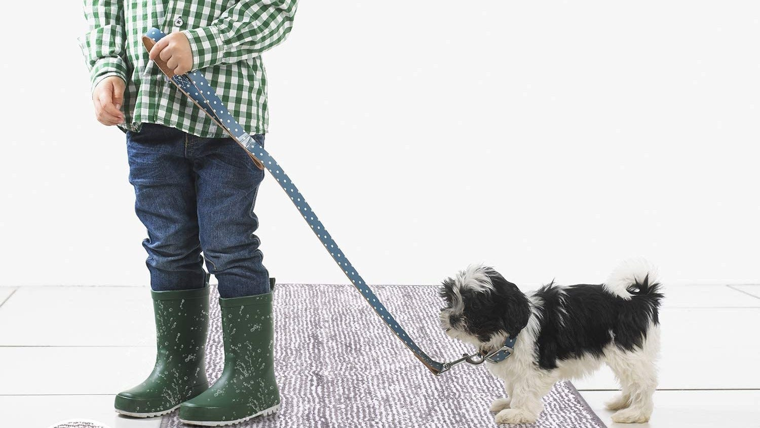 A man with wet boots standing on the Refetone Absorbent Mat with a leashed dog.