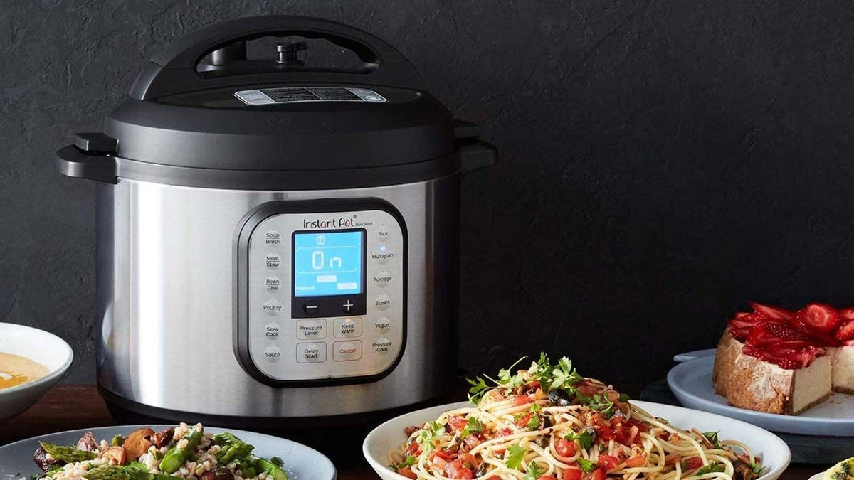 An instant pot on a table surrounded by dishes of food.