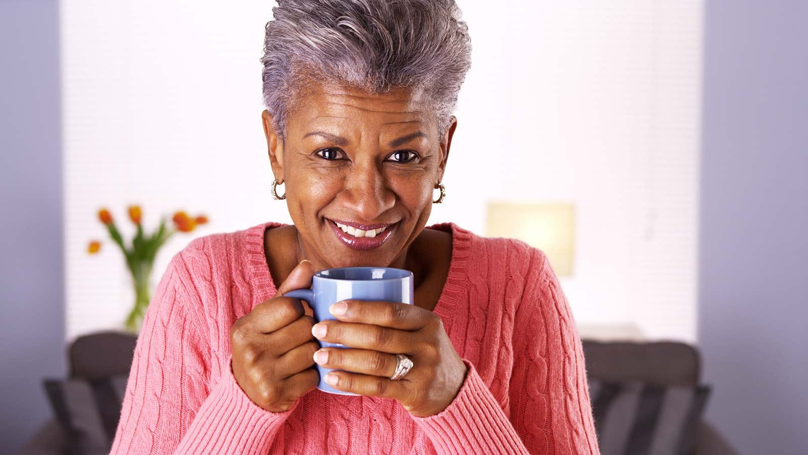 A grandmother drinking tea out of a pretty, lilac mug.