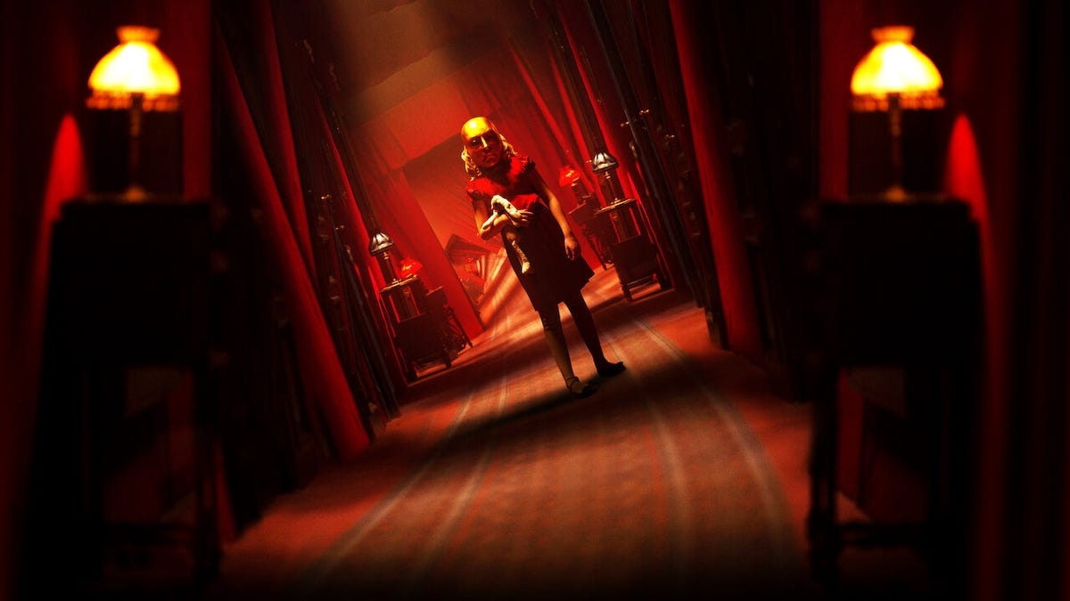A child stands wearing a golden mask in a spooky red hallway.