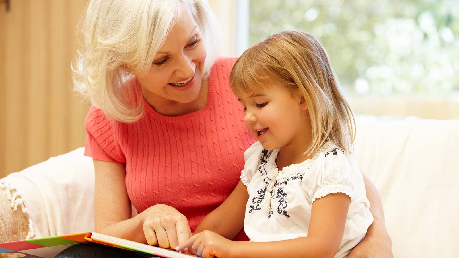 A grandmother reading a book to her granddaughter.