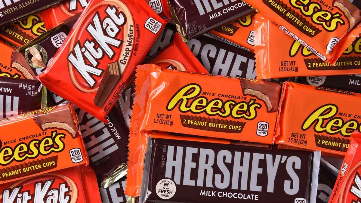 A collection of Reese's, Kit Kats, and Hersey bars are scattered in a group.