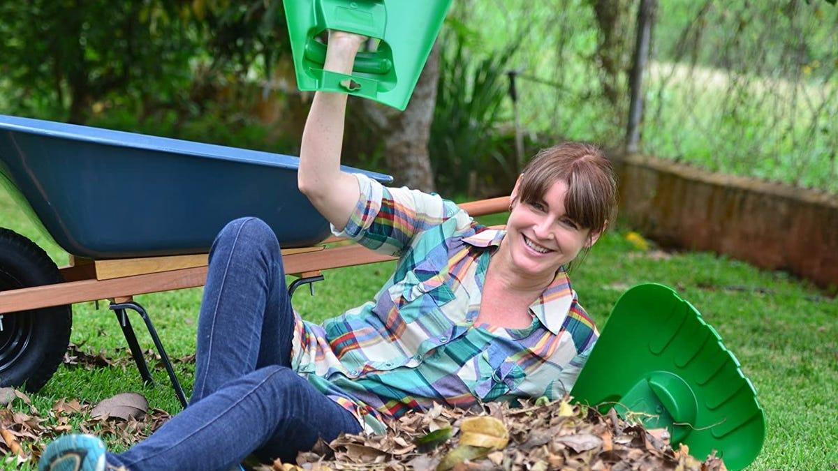 A woman lying on a pile of leaves, with leaf scoops on her hands.