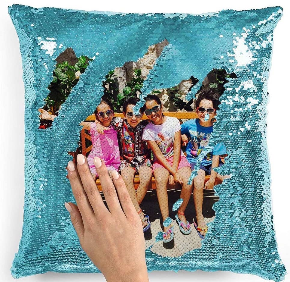 A turquoise sequined pillow with a picture of four kids sitting on a bench.