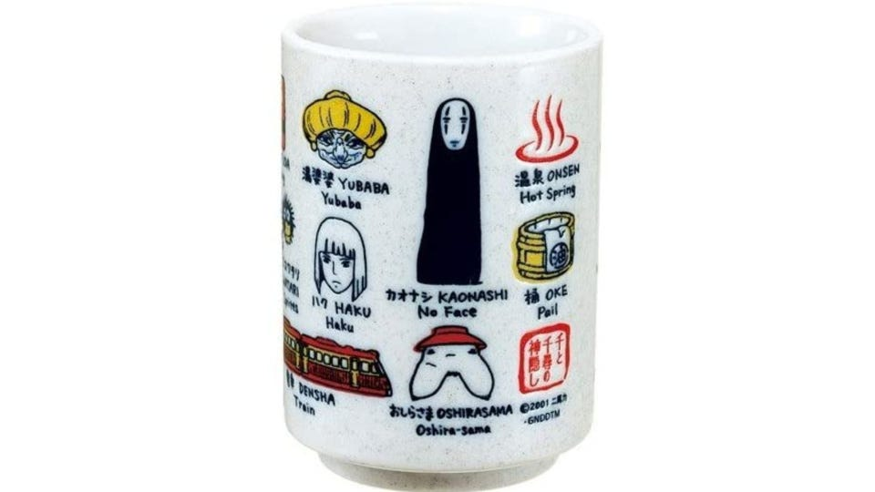 A light gray tea cup, covered with images from the hit film Spirited Away, Japanese and English words translated.
