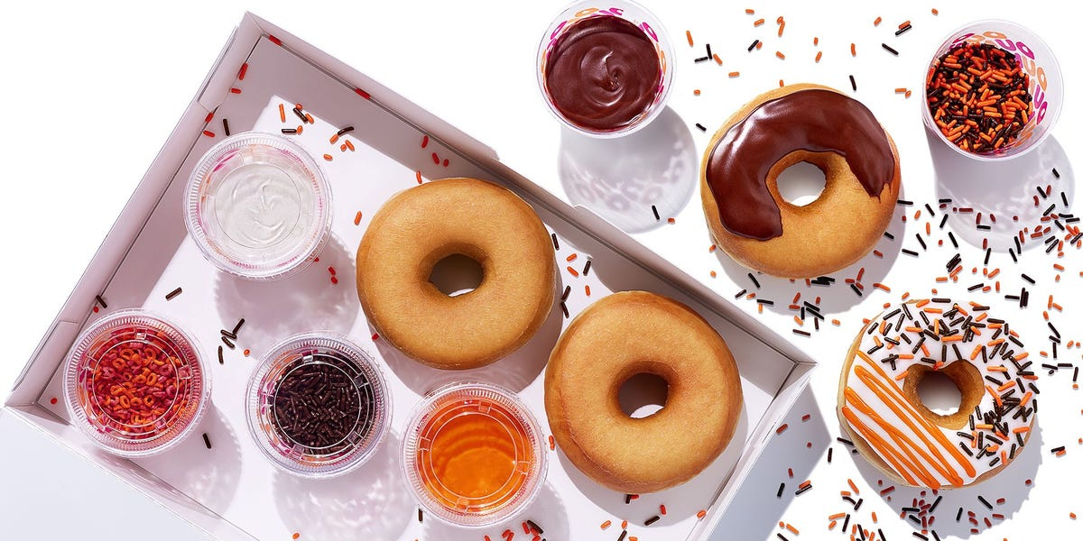 A box is filled with plain doughnuts, black, white, and orange icing, and sprinkles.