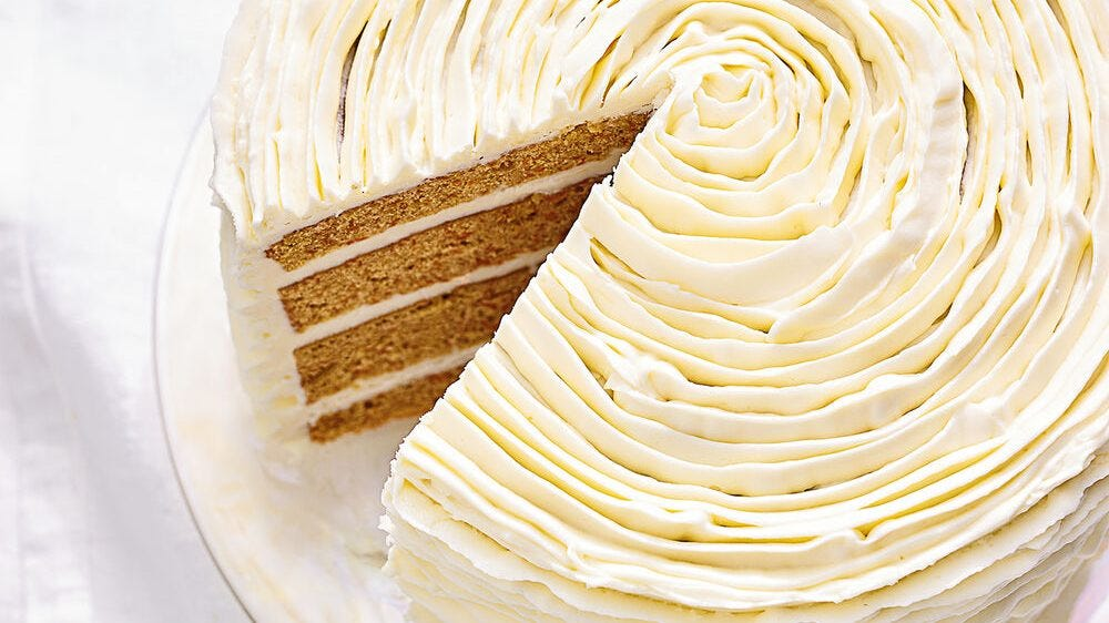 A white frosted cake sits on top of a table with a triangular piece cut out.