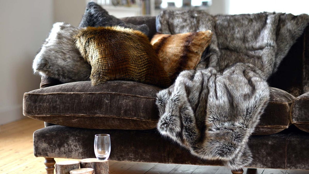 A cozy faux-fur throw blanket on a stylish couch.