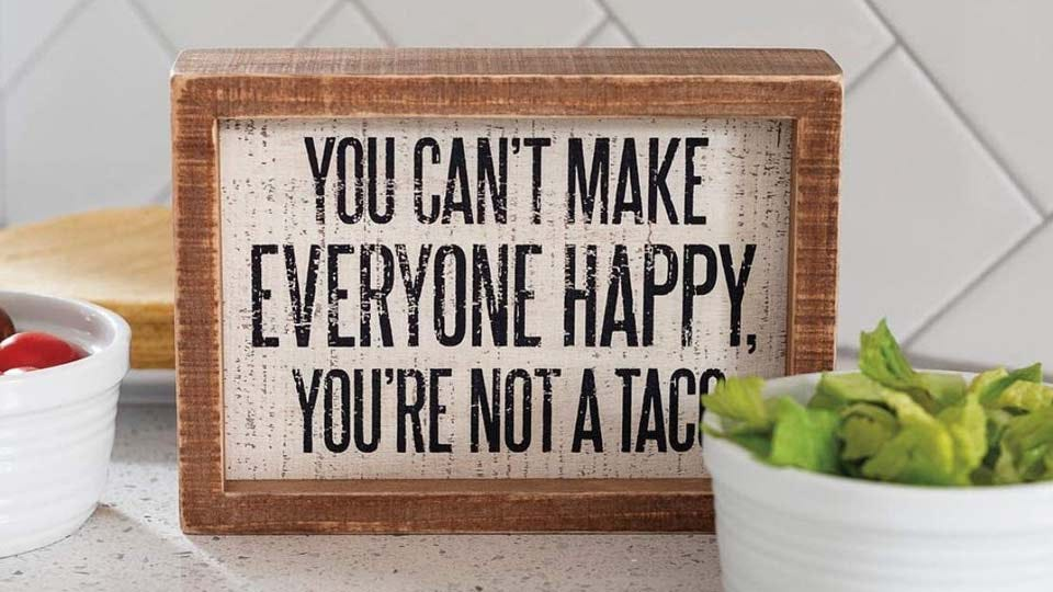 """A box sign that says """"You Can't Make Everyone Happy, You're Not a Taco."""""""