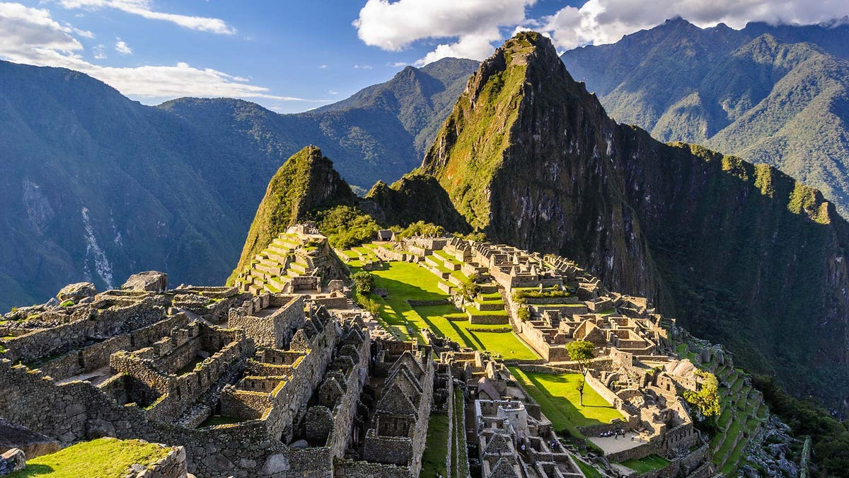 The ruins of Machu Picchu, a historical site nestled in the Andes mountains.