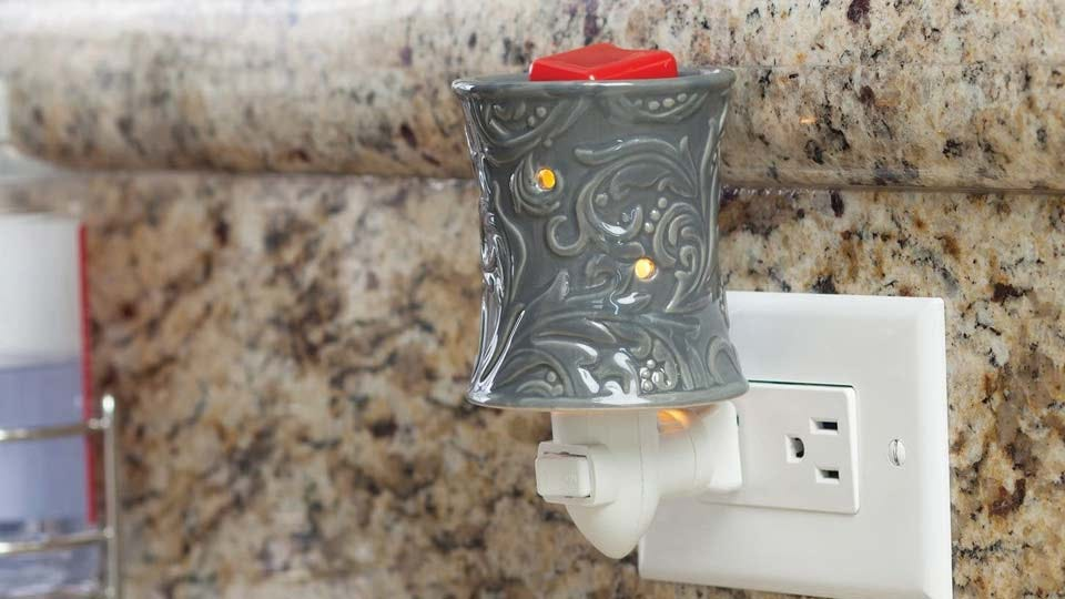 A candle wax warmer, plugged into an outlet.