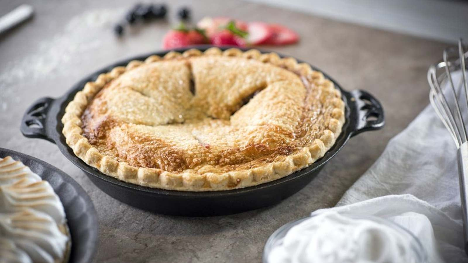 An apple pie cooling on a counter in the Camp Chef Cast-Iron Pie Pan.