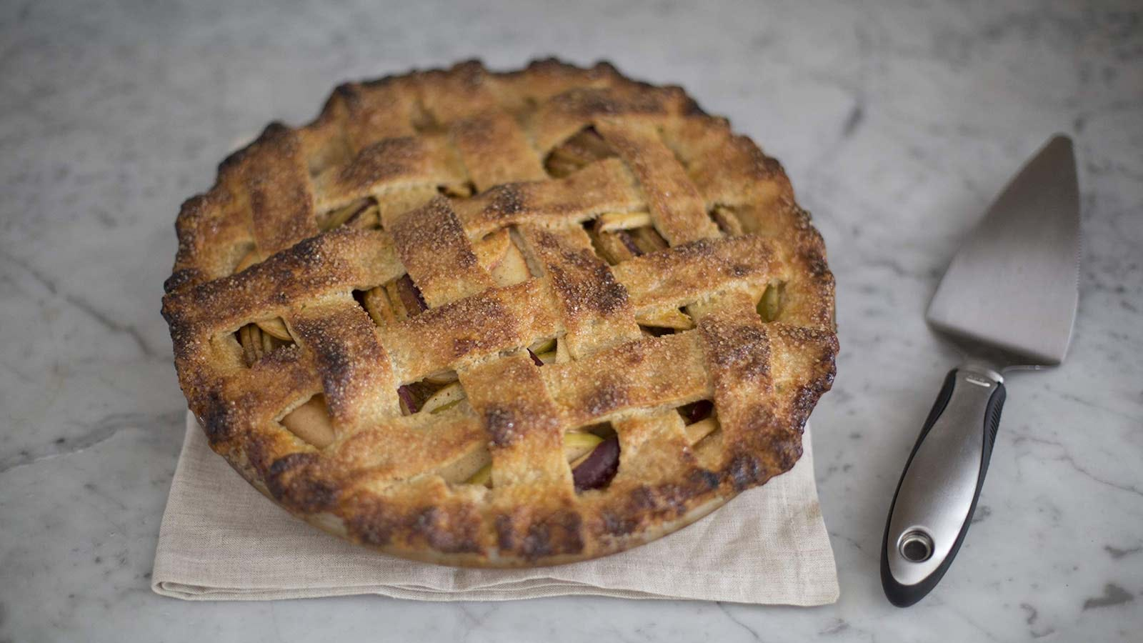 An apple pie on a counter with the OXO Steel Pie Server sitting next to it.