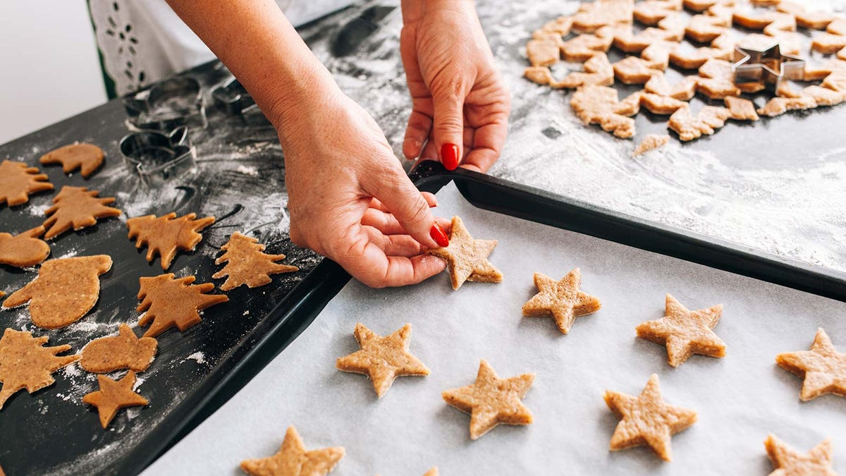 A woman placing Christmas cookies on a baking sheet.