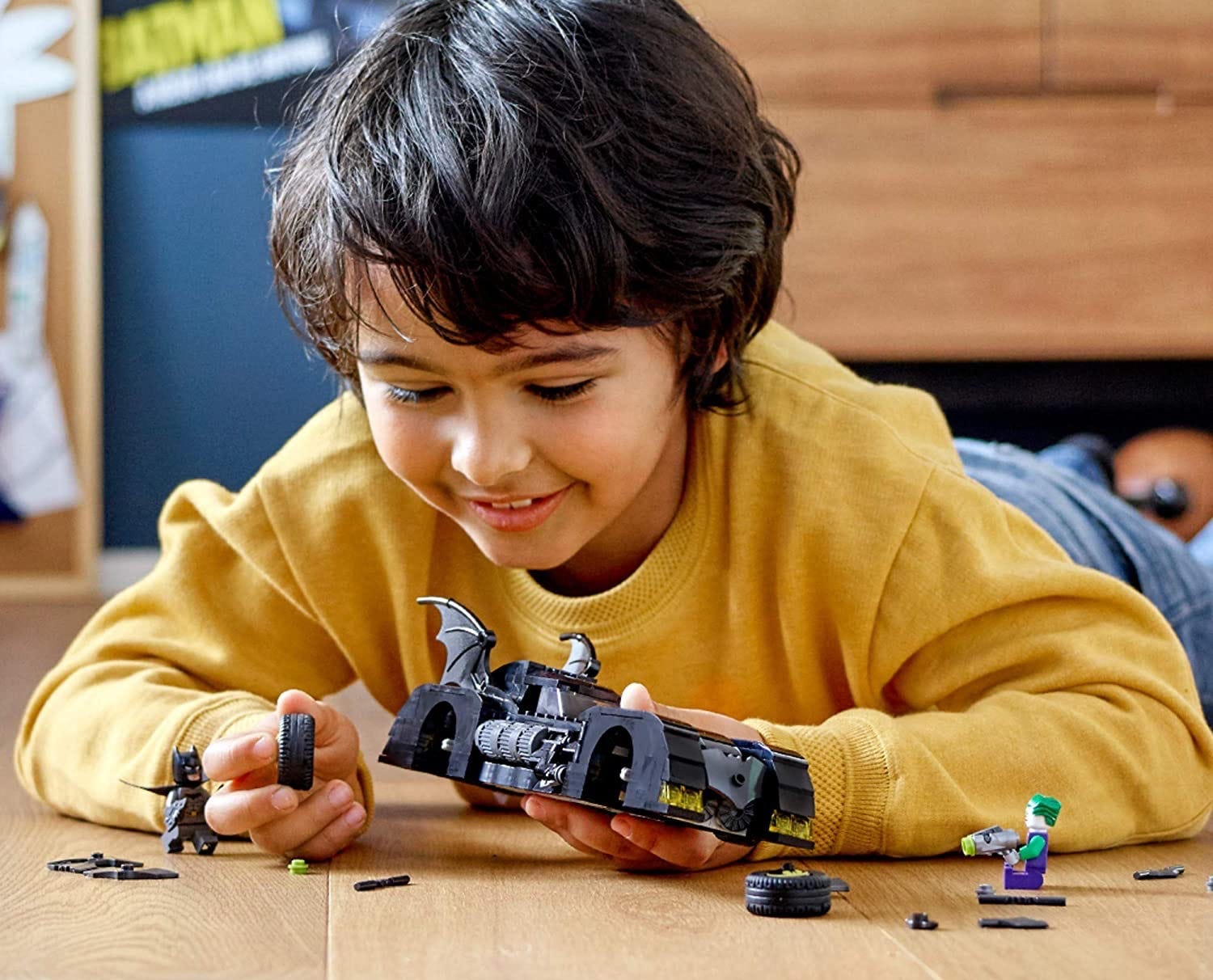 A young boy playing with a batmobile LEGO set.