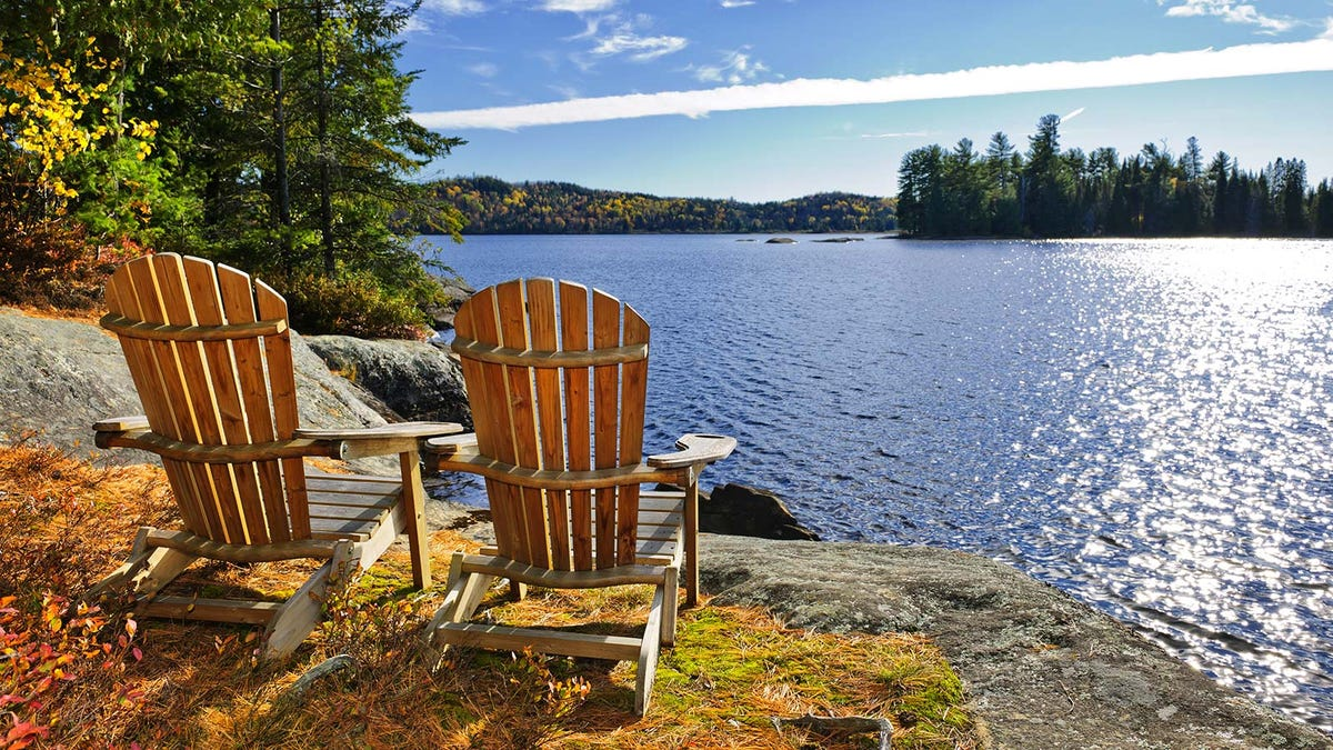 Two Adirondack chairs on a hill overlooking a lake.