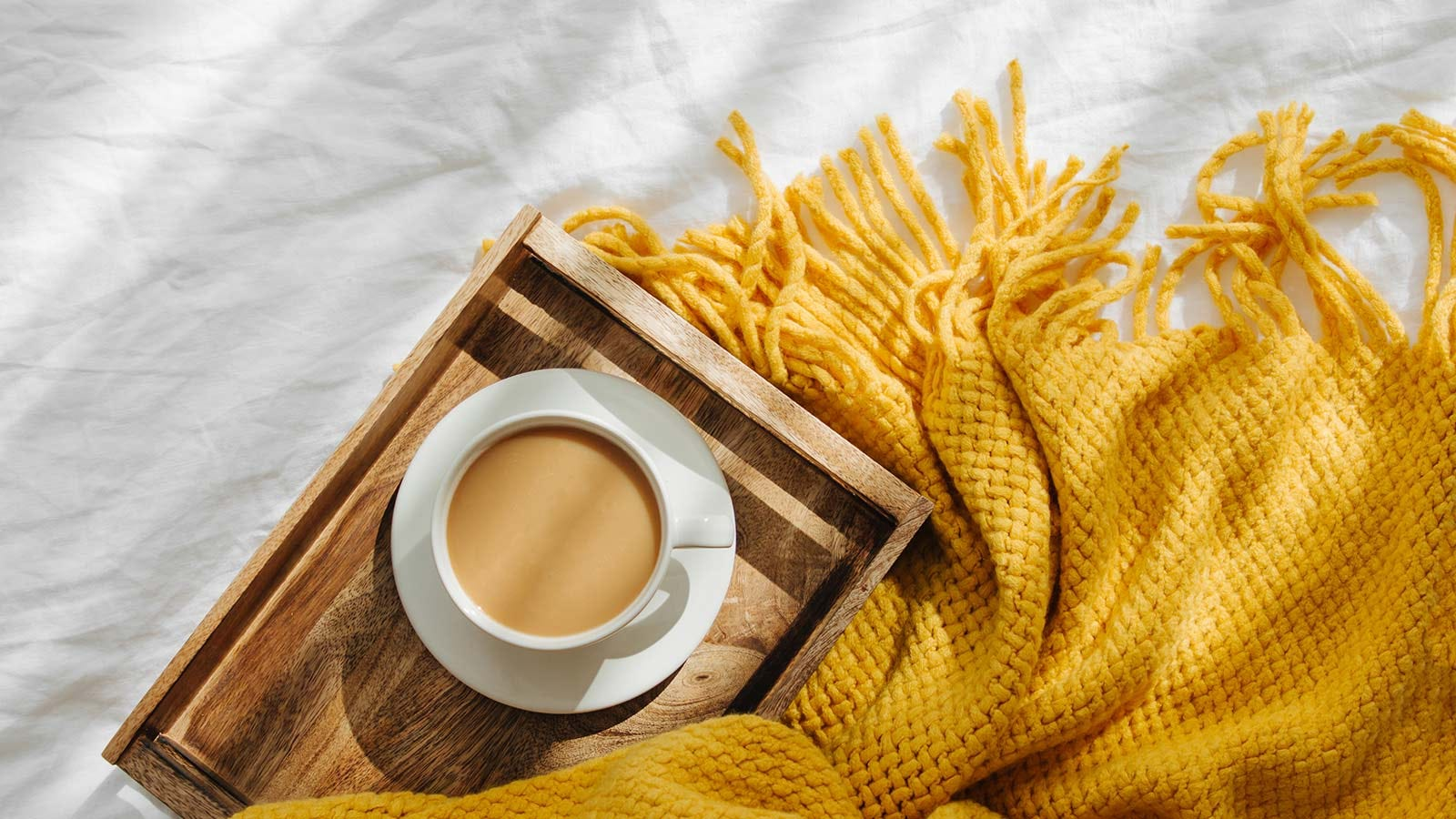 A wooden tray with a cup of coffee on it, sitting on a bed.