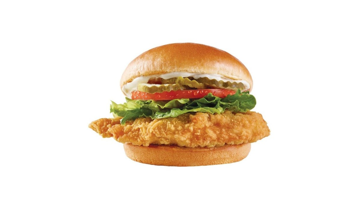 A Wendy's chicken sandwich with lettuce, tomato, mayo, and pickles sits on a white background.
