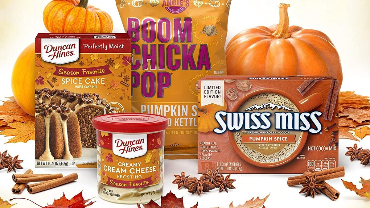 A box of Duncan Hines Spice Cake, a jar of Duncan Hines Creamy Cream Cheese Frosting, a pack of Angie's Boom Chicka Pop Pumpkin Spice Kettle Corn, and a box of Swiss Miss Pumpkin Spice Hot Cocoa Mix, surrounded by three pumpkins and cinnamon sticks.