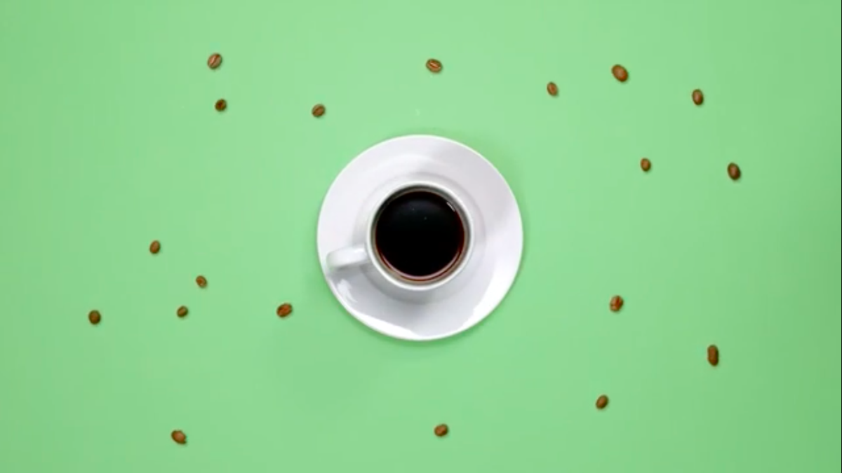 A white cup of coffee sits on a saucer surrounded by coffee beans.